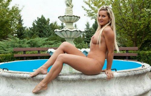 Голая блондинка возле фонтана
