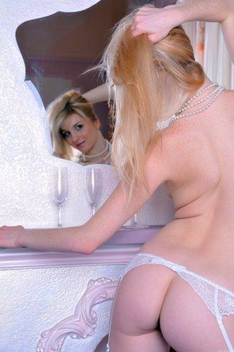 Молодая фотомодель Эльвира в белых чулках на фоне камина