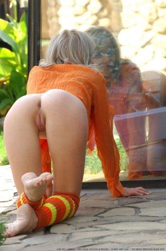 Обнажённая блондинка Mila принимает вызывающие позы во дворе у окна