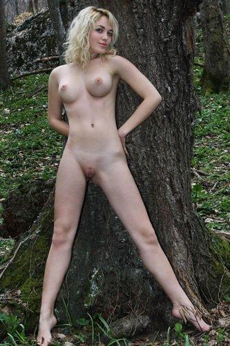 Раскрепощённая голая блондинка делает частные эротические фото в лесу