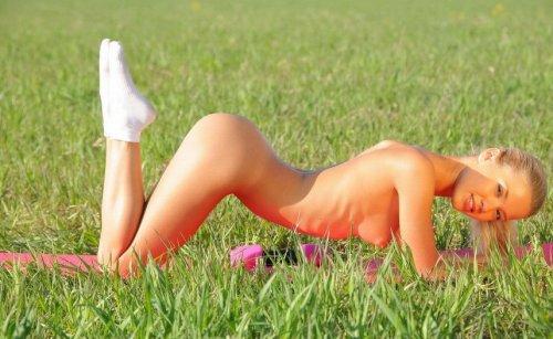Стройная блондинка занимается физкультурой в поле