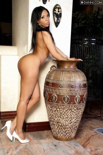 Темнокожая красавица с соблазняющей попкой снимает трусики в гостиной