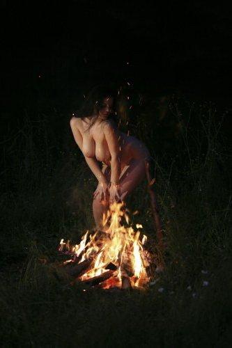 На частных эротических фото полненькая голая девушка танцует у костра ночью