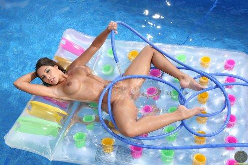 Сисястая девушка Zafira поливает бритую вагину холодной водой с шланга в бассейне