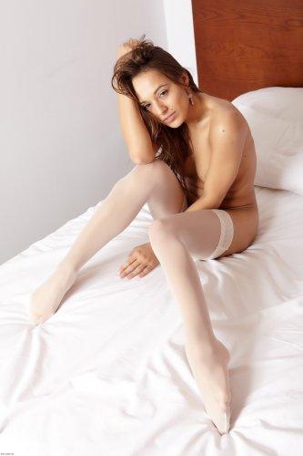 Стройная брюнеточка Dominika на кровати в белых чулках