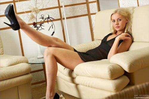 Худая девушка Sarah с бритой писей сексуально позирует на диване