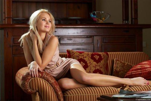 Белокурая красавица Talia без одежды на эротических фото в гостиной