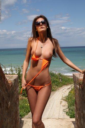 Загорелая красотка Barbara в очках делает эротические фото на пляже
