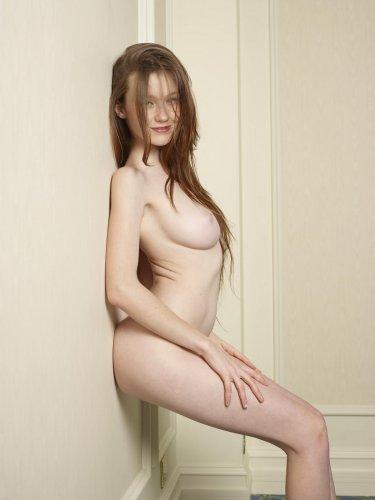 Голая красотка Emily натуральной красоты делает эротические фото у стены
