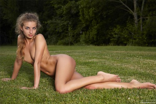 Худенькая обнажённая девушка Саша делает фотографии на зелёной лужайке
