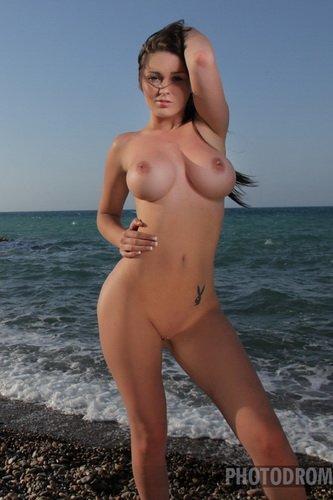 Эротические фото Eva T с силиконовыми сиськами и стройным телом на пляже