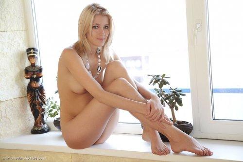 Симпатичная голая блондинка Mila Zerra показывает эротику у окна
