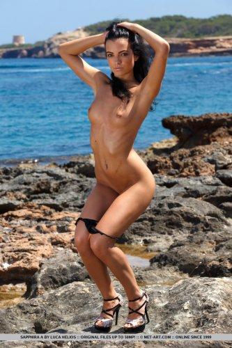 Брюнетка Sapphira A сняла чёрный купальник и раздвинула ноги на камнях