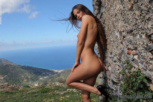 Стройная красавица Juliette снимает платье на скалистых холмах