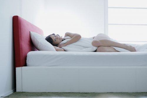 Хрупкая фотомодель Kalea Taylor лежит обнаженная на кровати утром