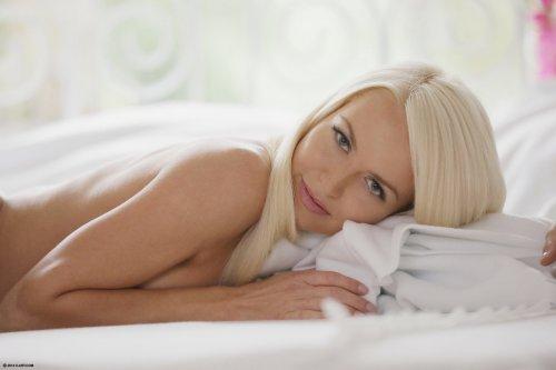 Крутая блондинка Lena Love снимает белые кружевные трусики в спальне