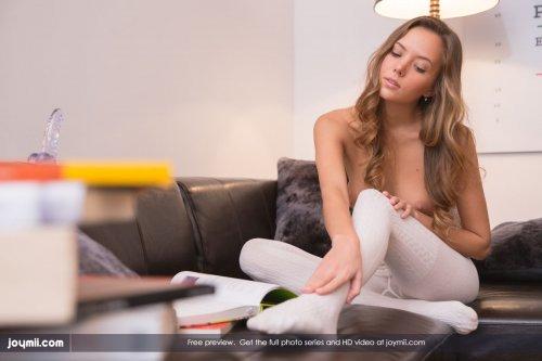 Скромная модель Katya Clover снимает белые колготки на чёрном кожаном диване