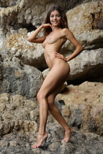Divina A позирует обнаженной на фоне скал